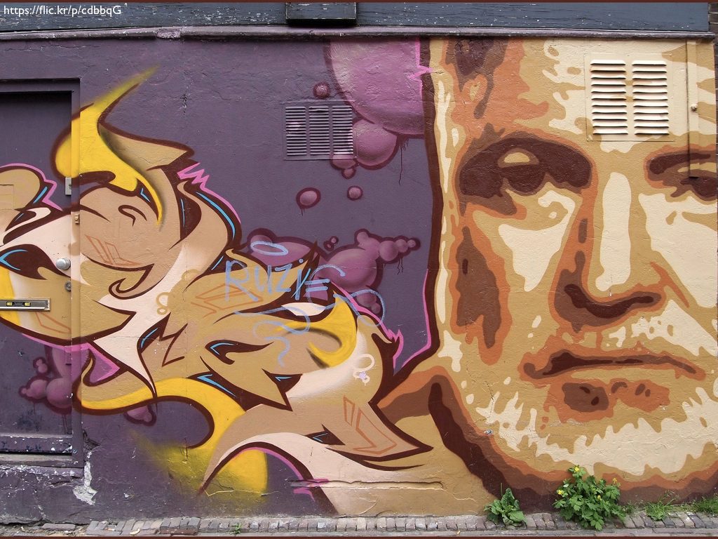 A street art mural of Hemingway's face against the side of a building.