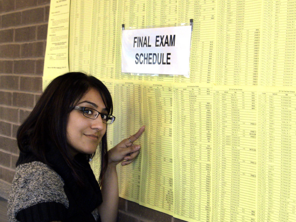 A woman pointing at a 'Final Exam Schedule' list papered against a red brick wall