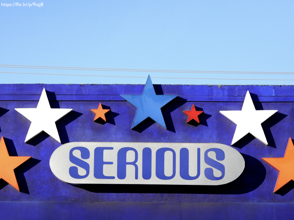 A brightly painted building iwth the word 'SERIOUS' on a sign surrounded by stars.