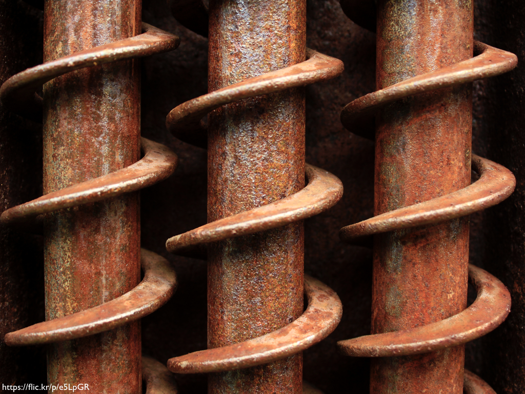 A close-up image of large threads on rusted screws