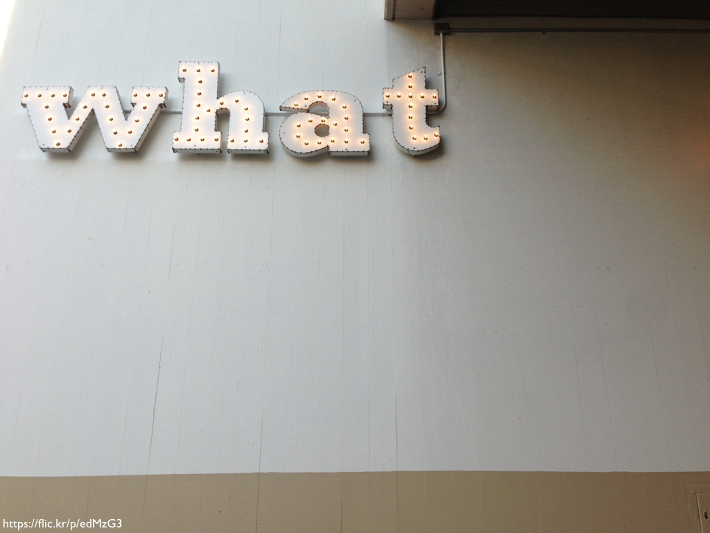 The word 'what' spelled out in light-up letters on the side of a building.